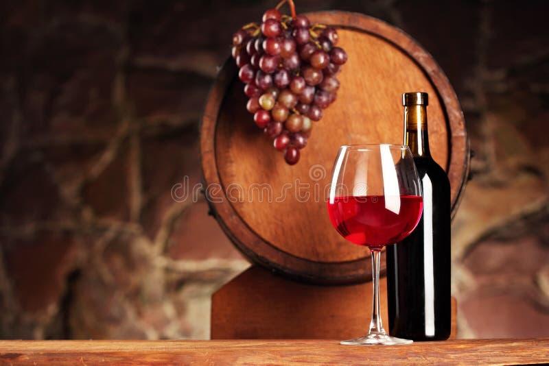 查出的om红色waite酒 与玻璃和瓶的静物画红酒、葡萄和桶 选择聚焦 葡萄酒库大气 复制空间 免版税库存照片