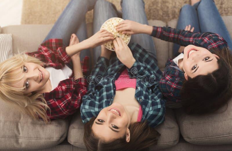 查寻三名的妇女吃玉米花和,顶视图 库存图片