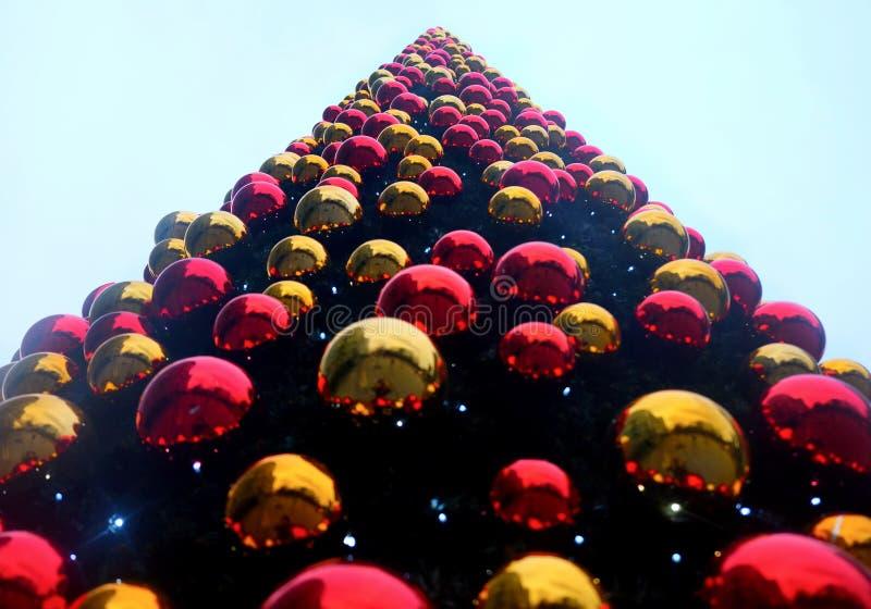 查寻从在被盖的一棵非常大圣诞树的上面的底部在数百红色和金子圣诞节中看不中用的物品 免版税图库摄影