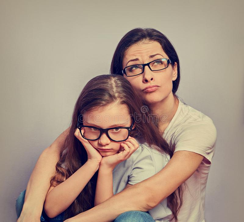 查寻和拥抱她紫罗兰色墙壁背景的哀伤的年轻偶然母亲逗人喜爱的不快乐的被触犯的想法的孩子女孩 ?? 库存图片