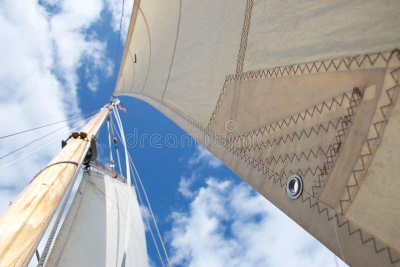 查寻在一条航行的游艇的帆柱;集中于在风帆的一个小孔 免版税库存图片