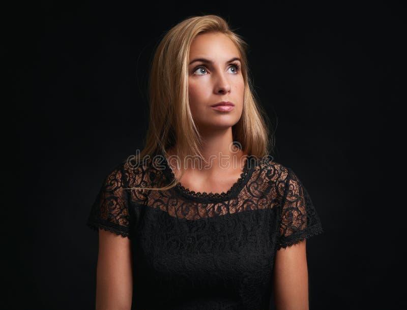 查寻在黑背景的俏丽的妇女 免版税库存照片