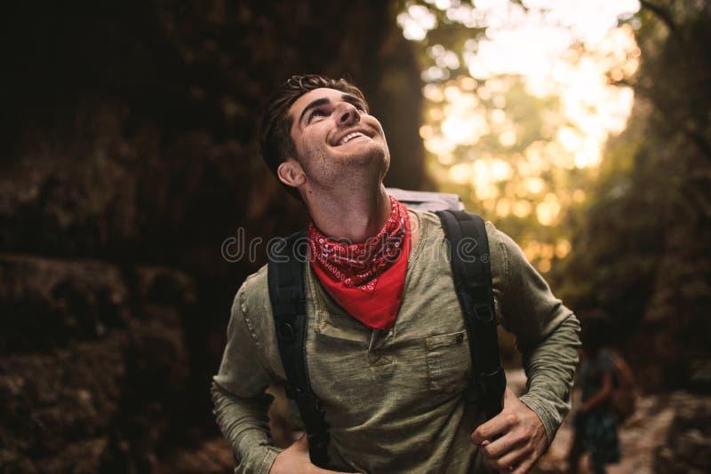 查寻微笑的年轻的人步行在山和 库存图片