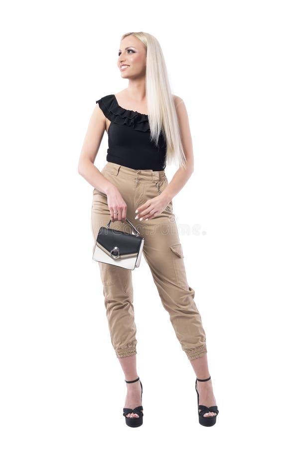 查寻时髦的美丽的年轻白肤金发的妇女藏品的钱包微笑和 库存照片