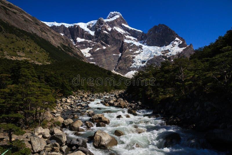 查寻融化水放出往在托里斯del潘恩国家公园围拢w步行足迹的垂悬的冰川 图库摄影
