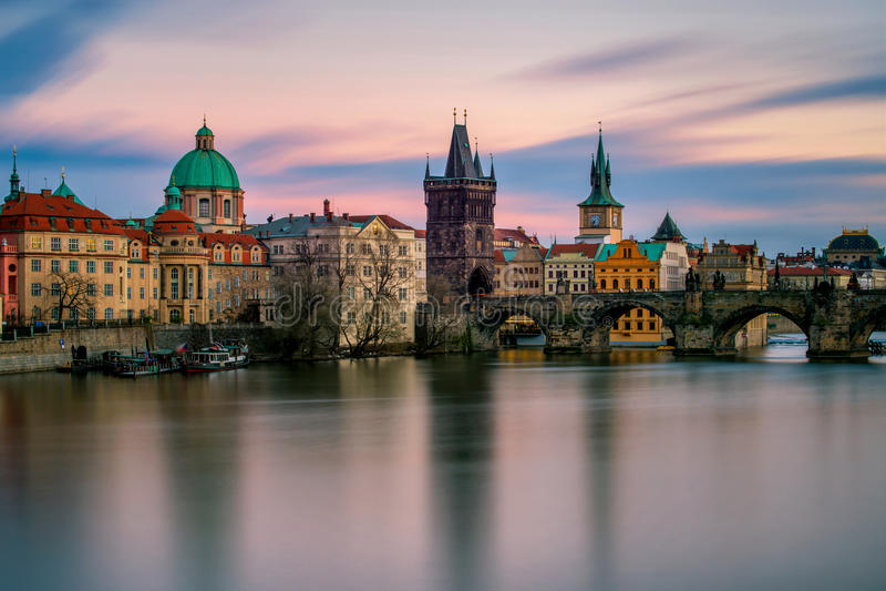 查尔斯桥梁惊人的塔有反射的在多云日落期间的伏尔塔瓦河河,布拉格,捷克共和国 免版税库存图片