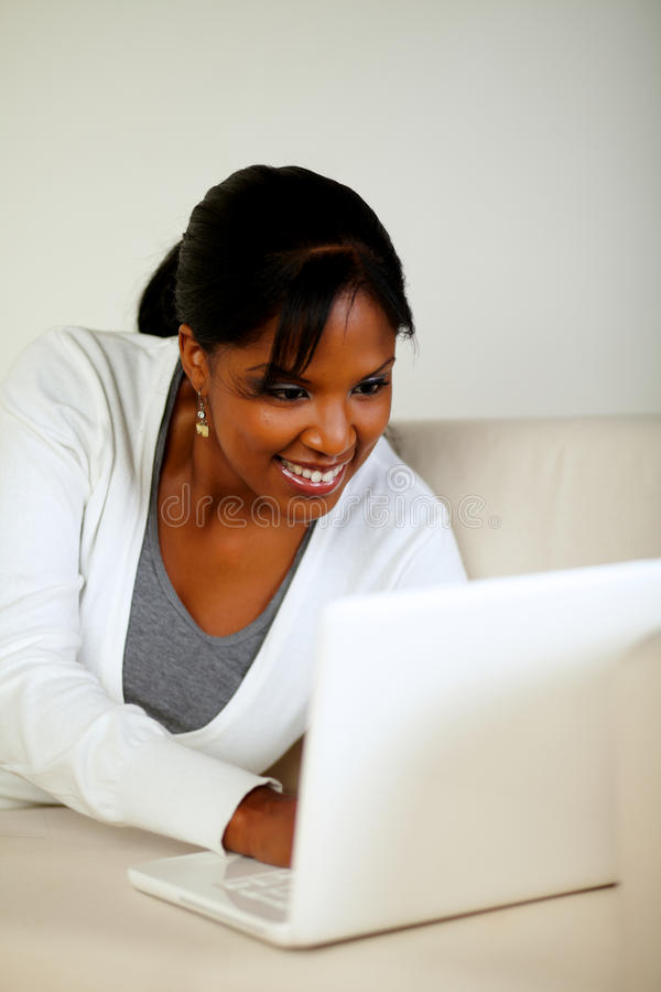 查找在膝上型计算机屏幕的微笑的黑人妇女 免版税库存照片
