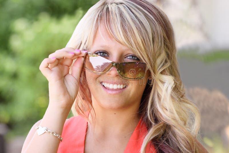 查找在sunnglasses少年的接近的女孩 免版税图库摄影