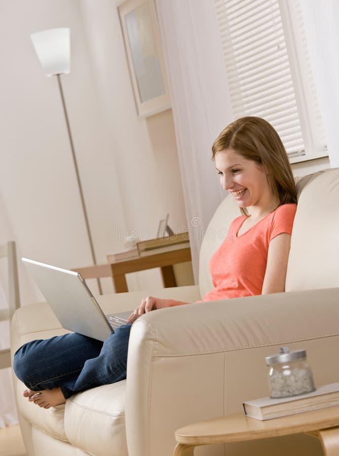查找妇女年轻人的家庭膝上型计算机 免版税库存照片