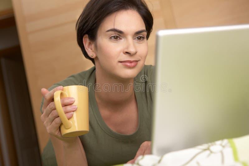 查找屏幕微笑的妇女的家庭膝上型计&# 免版税库存图片