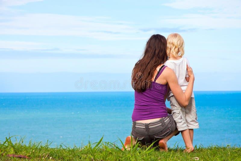 查找母亲海景的漂亮的孩子 库存图片
