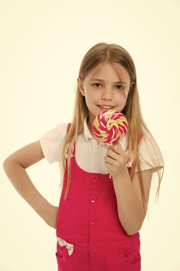 查找甜 女孩吃在棍子的糖果在白色 与棒棒糖的儿童微笑 愉快的孩子用漩涡焦糖 库存照片