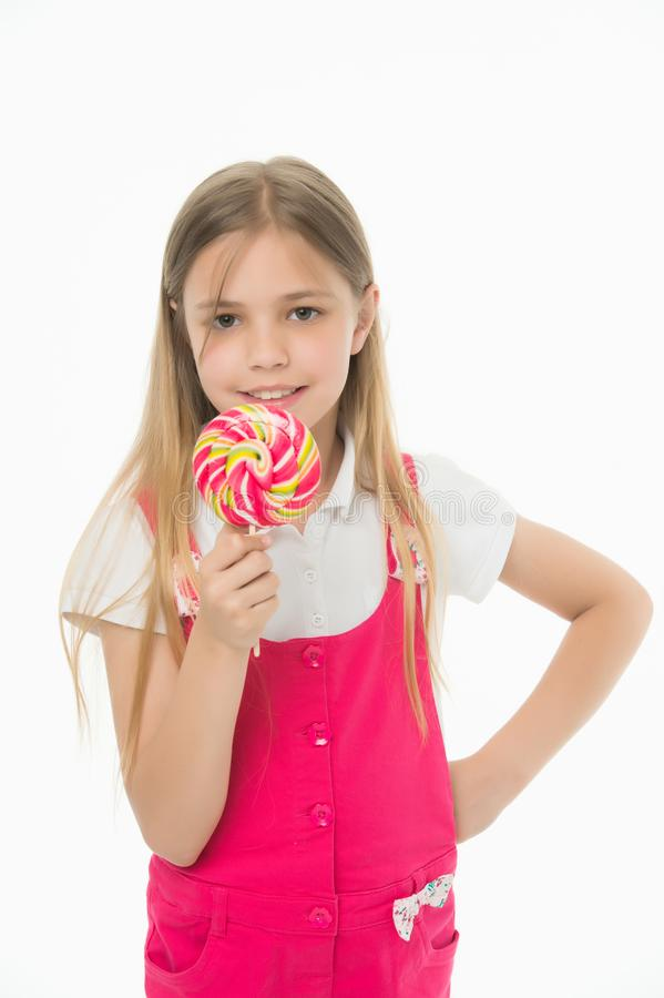 查找甜 小女孩吃在白色隔绝的棍子的糖果 与棒棒糖的儿童微笑 愉快的孩子用漩涡焦糖 免版税库存图片