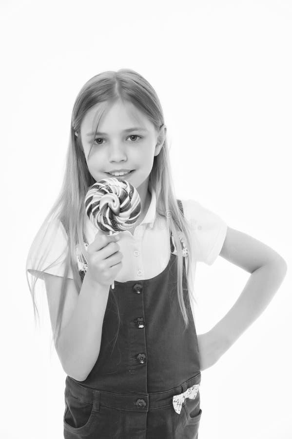 查找甜 小女孩吃在白色隔绝的棍子的糖果 与棒棒糖的儿童微笑 愉快的孩子用漩涡焦糖 库存图片