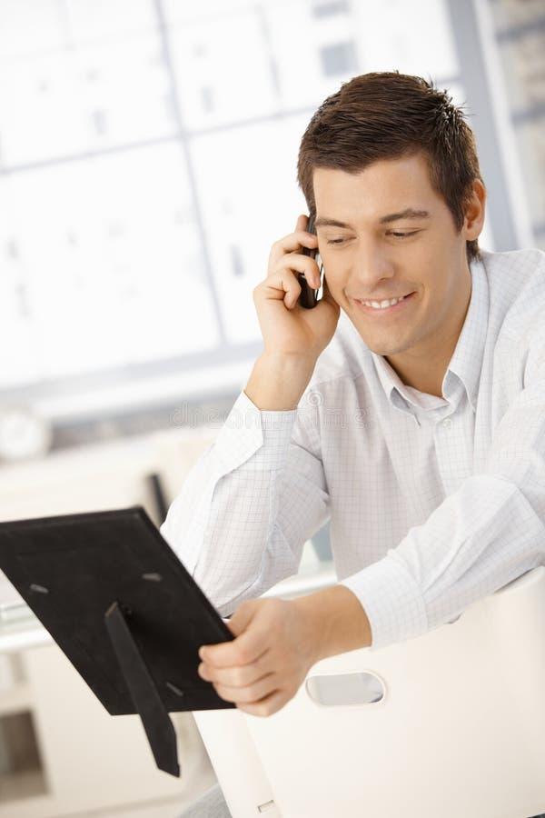 查找电话照片的生意人框架 图库摄影