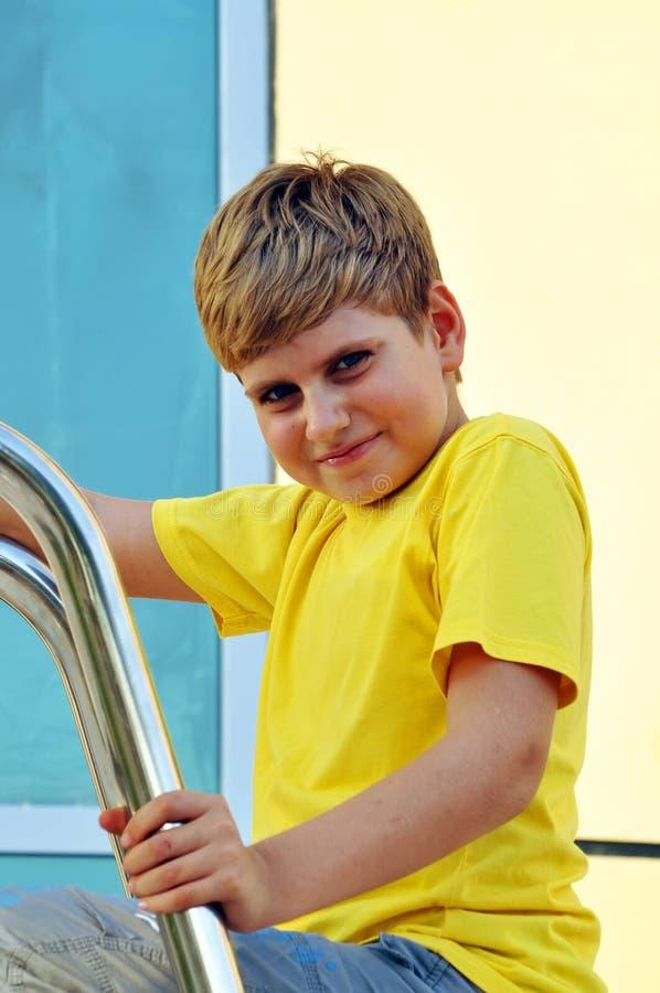 查找纵向的白肤金发的男孩照相机smilling 免版税库存图片