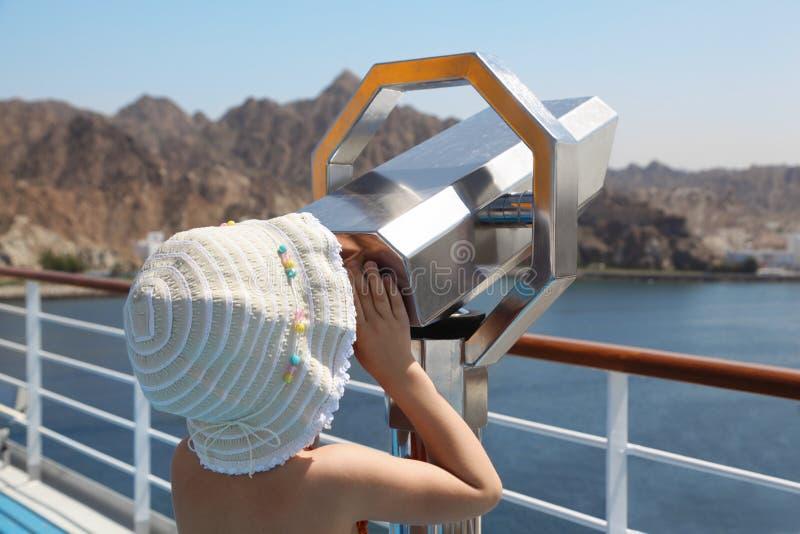 查找船望远镜的甲板女孩 免版税库存图片