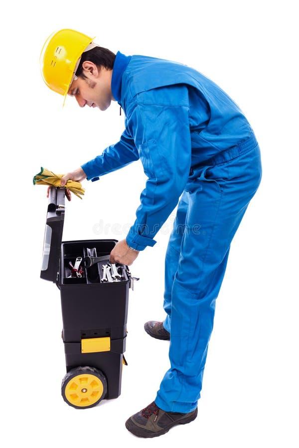 查找通过他的工具箱的新建筑工人 免版税库存照片