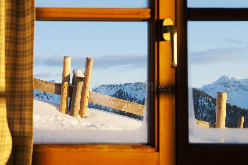 查看冬天的瑞士山中的牧人小屋田园诗横向 图库摄影