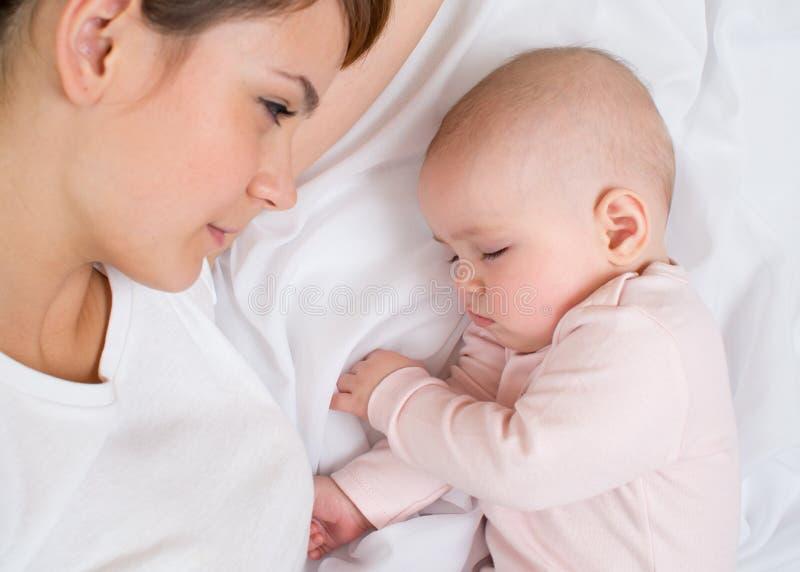 查看她休眠的女婴的新母亲 库存图片