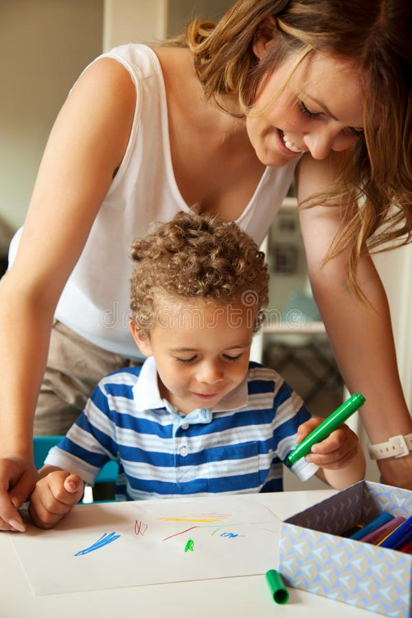 查看孩子的图画的学龄前教师 库存照片