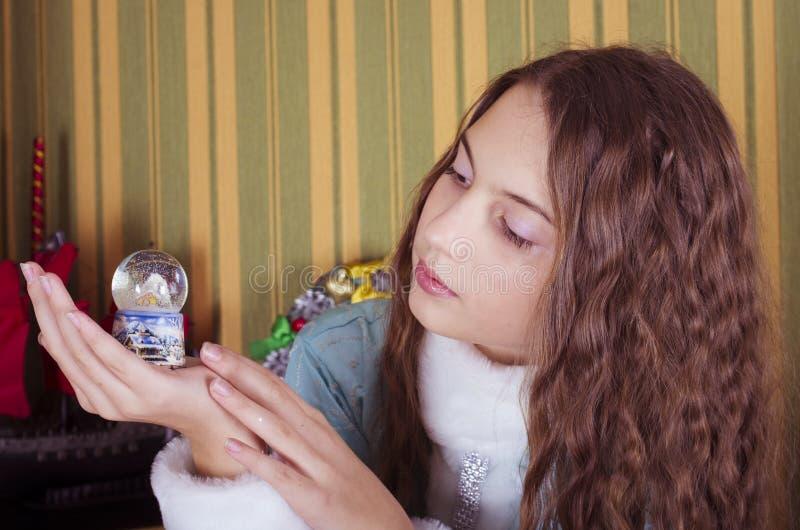 查看雪地球的青少年的女孩 免版税图库摄影
