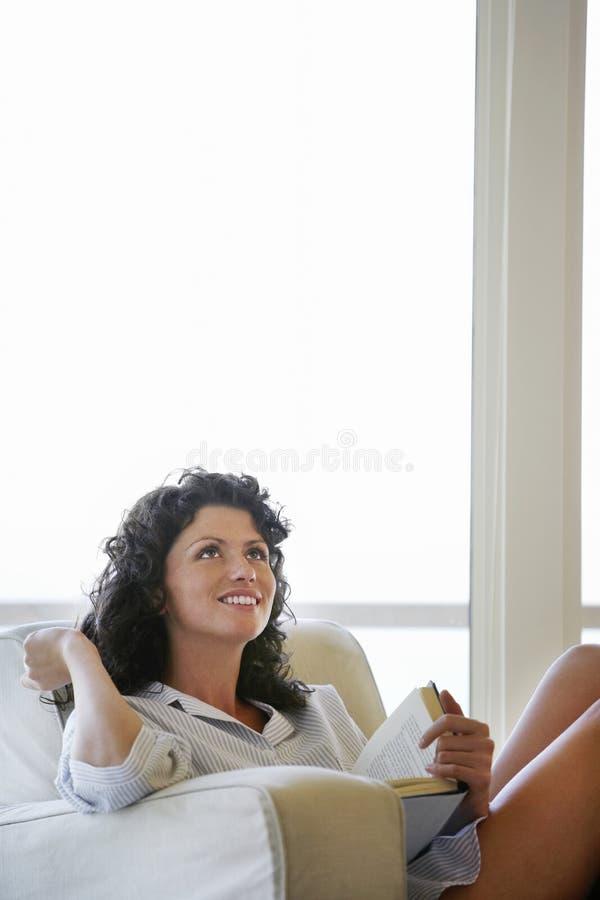 查寻体贴的妇女,当放松在扶手椅子时 库存图片
