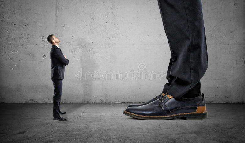 查寻在另一个人的巨大的腿的微小的商人 库存照片