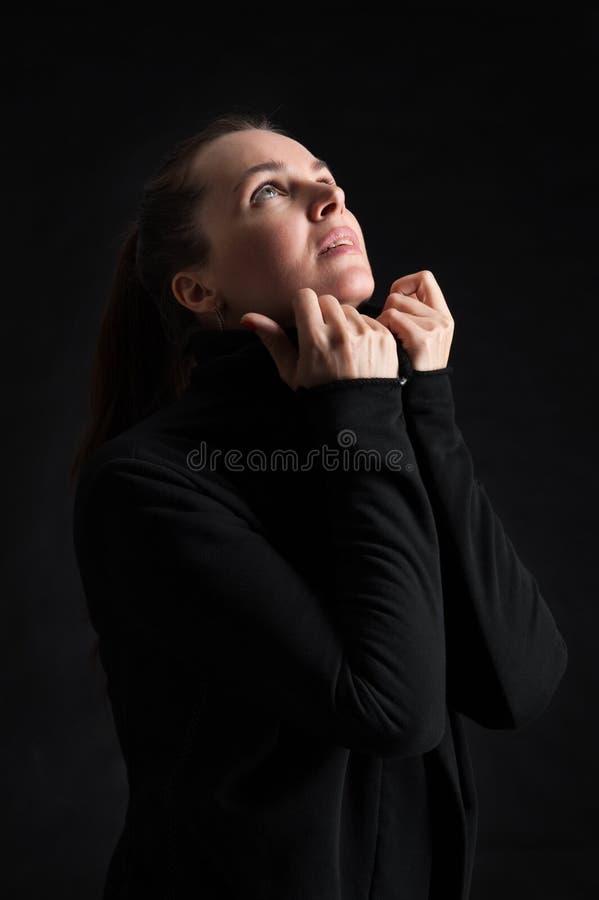 查寻在黑暗的深色的妇女 祈祷 库存照片