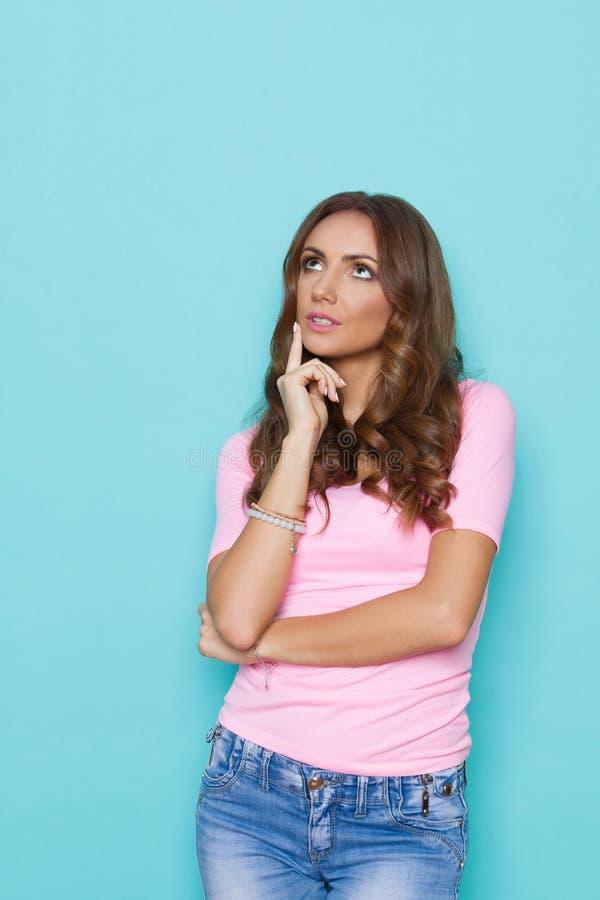 查寻粉红彩笔的衬衣的沉思少妇 免版税图库摄影