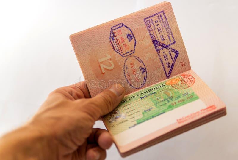 柬埔寨在俄国护照的签证图章在人的手上 库存照片