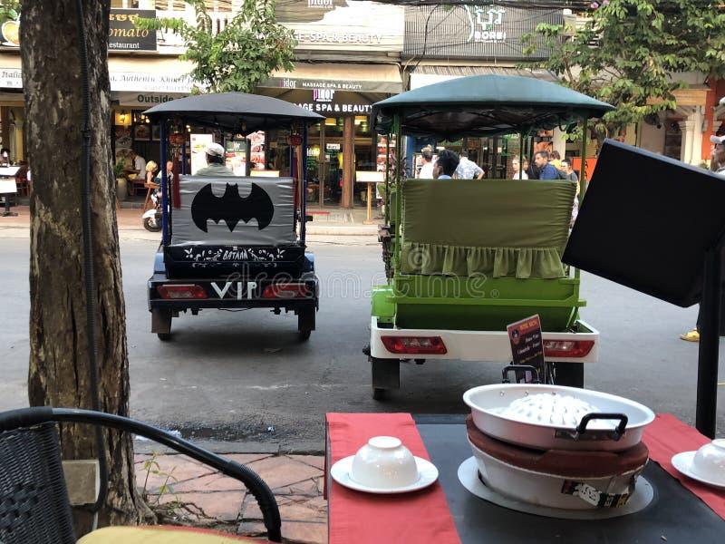 柬埔寨暹粒黑色VIP蝙蝠侠Tuk Tuk在大街上的绿色一旁边停放 免版税库存照片