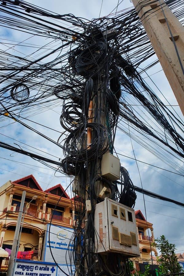 柬埔寨,暹粒市在输电线,被缠结的城市通信,电源的问题的12/08/2018混乱 免版税库存照片