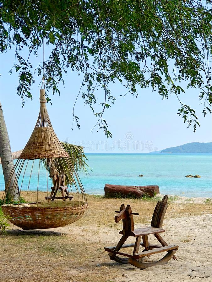 柳条吊床和木摇马在一个热带海滩 免版税库存照片