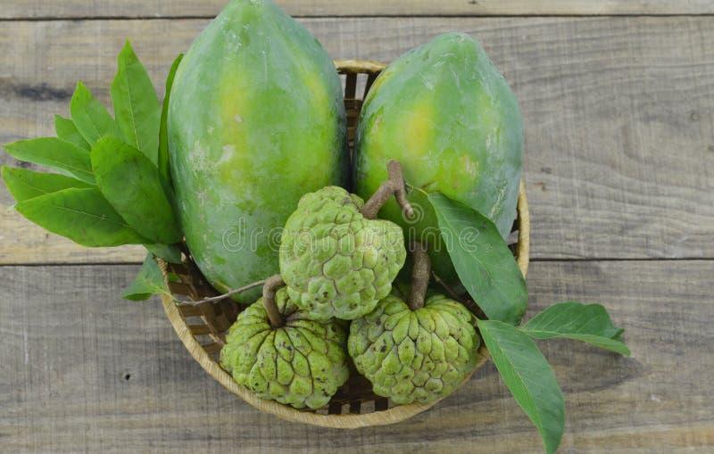 柳条筐用绿色番木瓜和南美番荔枝在木背景 库存照片