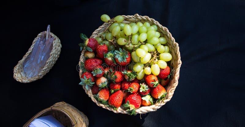 柳条筐用草莓和新鲜的葡萄 库存图片