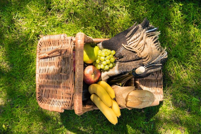 柳条野餐篮子顶视图用果子、酒瓶和格子花呢披肩在绿色草坪 图库摄影
