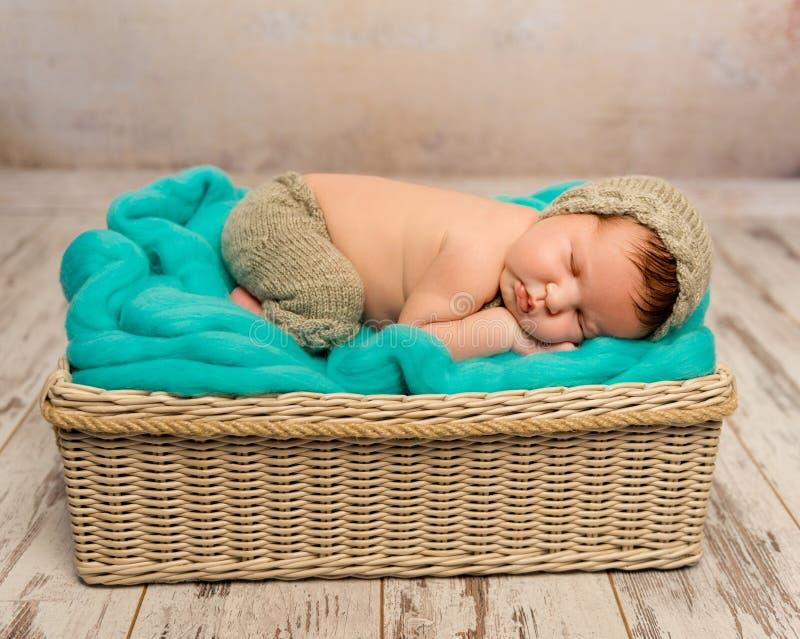 柳条轻便小床的滑稽的睡着的新出生的婴孩 免版税图库摄影
