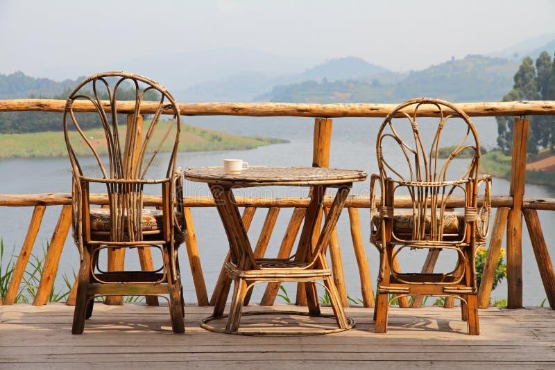 柳条轻便折叠躺椅用在表和湖视图上的咖啡 图库摄影