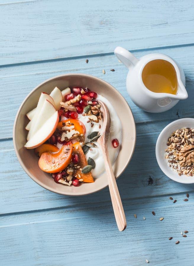 柿子、苹果、核桃、石榴、种子和自然酸奶 在蓝色背景,顶视图的健康食物概念 果子和gr 库存照片