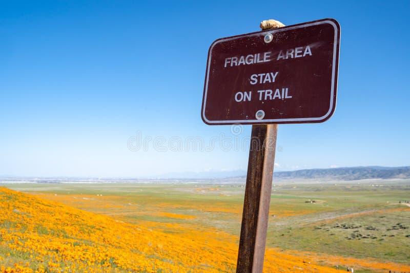 标志在加利福尼亚提醒访客停留在足迹在鸦片储备领域 免版税库存照片