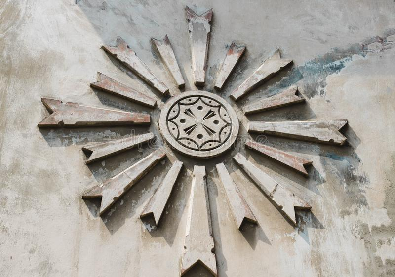 标志太阳是抽象的在灰色混凝土,水泥墙壁 一个古老标志 库存照片