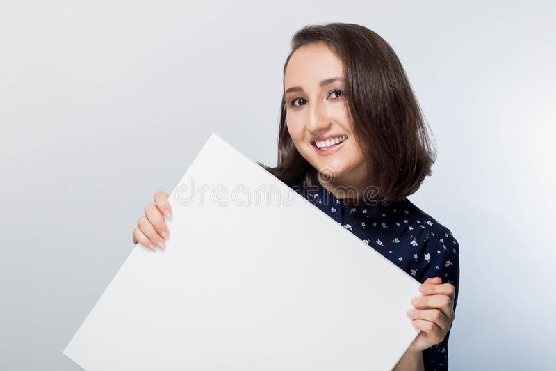标志板 拿着白人妇女的名片 查出的纵向 拿着一张空白的纸片副词的年轻愉快,微笑的女孩 免版税库存图片