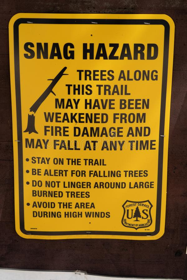 标志警告一种断枝危险的徒步旅行者沿树的,由于火灾损失,有些树也许落在其中任一 免版税库存照片