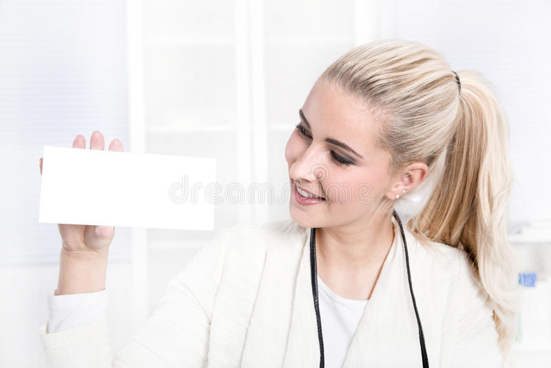 标志:拿着名片的白肤金发的妇女。 免版税库存图片