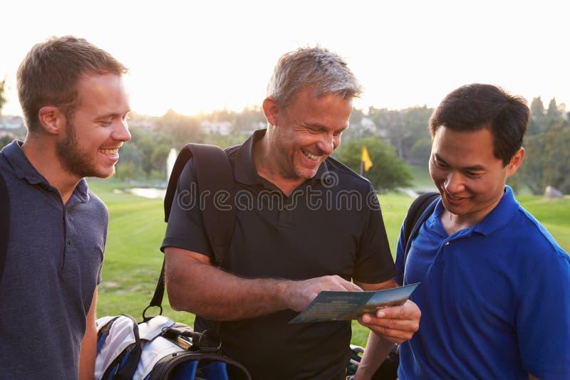 标记计分卡的小组男性高尔夫球运动员在圆结束时 库存图片