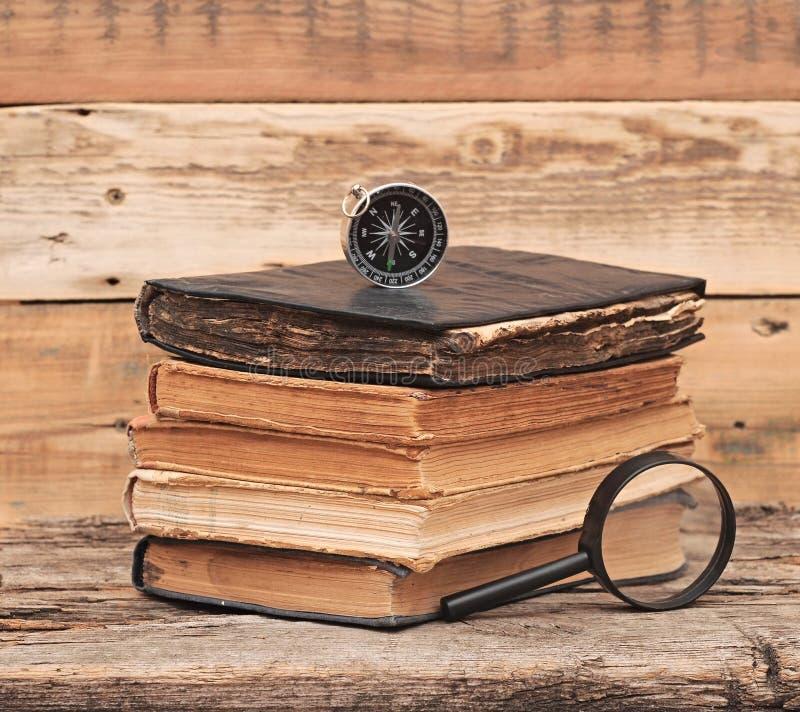 栈与放大镜的古色古香的书 免版税图库摄影
