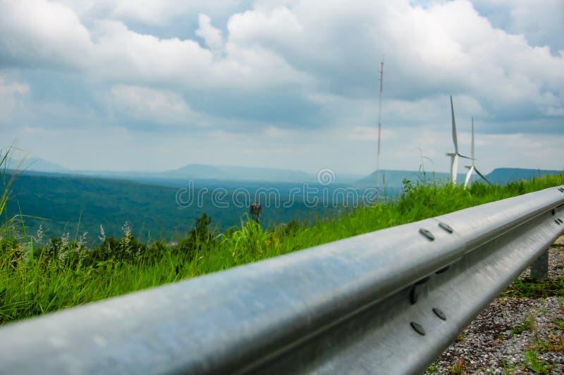 栏杆在与风轮机的路边在山、蓝天和云彩,风力驻地 生态学能源 库存图片