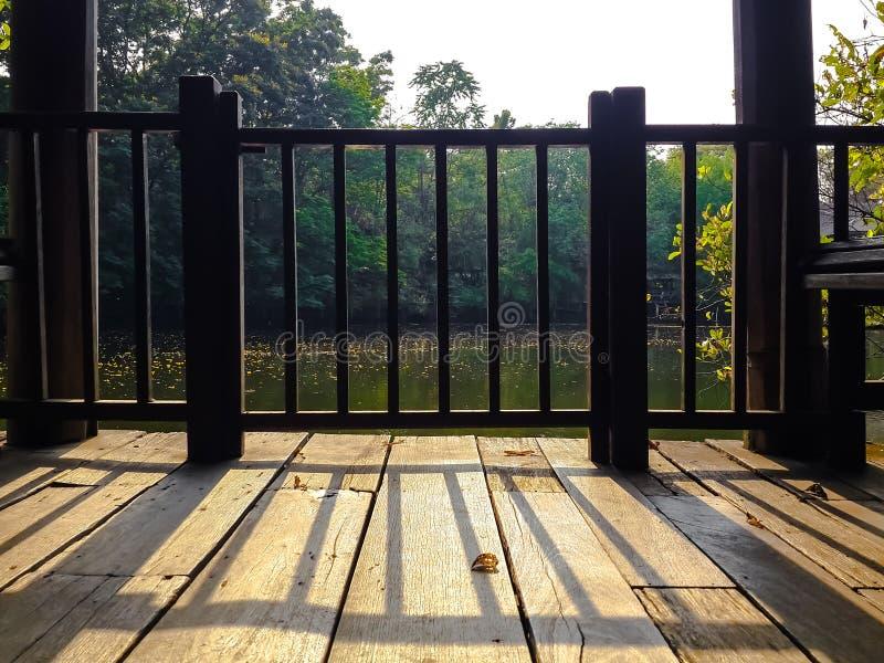 栏杆在葡萄酒木阳台地板上的阴影铸件 库存图片