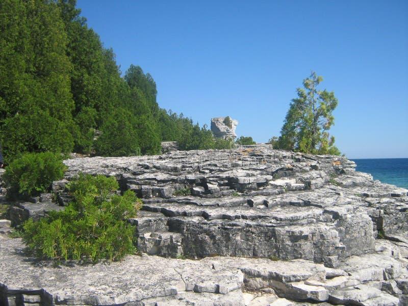 树、岩石、湖和蓝天 免版税库存照片